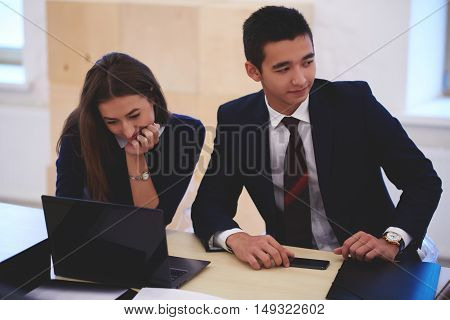 Woman is searching in net-book needed information for meeting with client while is sitting with partner in co-working space. Businessman is waiting customer and his secretary is using laptop computer