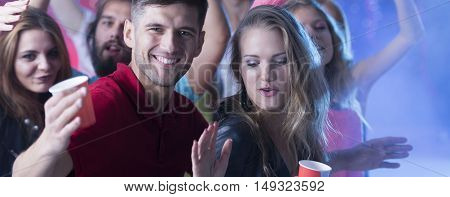 Blonde woman dancing close to the man during the party