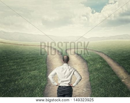 businessman look at crossroad in country road