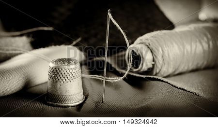 Sewing. Thimble, thread a needle and fabric