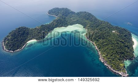 Aerial photo from flying drone of a green island in open sea with calm waves. Amazing nature landscape with Indian Ocean in sunny summer day. Unforgettable vacation in Thailand. Perfect background