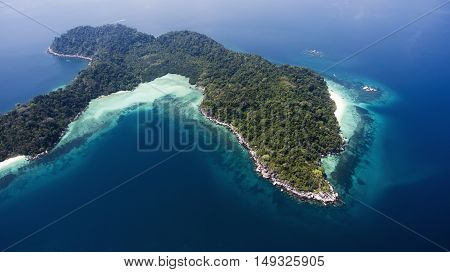 Aerial photo from flying drone of a fascinating view on a green island with tropical plats and white sand in Indian Ocean in sunny day. Perfect place to stay during summer vacation holidays.