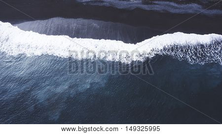 Top view aerial photo from flying drone of a beautiful landscape of a volcanic beach with black sand and sea with amazing white swell waves for surfing training. Wonderful Indian Ocean scenery