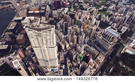 Top view aerial photo from flying drone of a developed metropolis city with tall office skyscraper with modern exterior design. Big megapolis with advanced buildings and transportation infrastructure