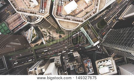 Top view aerial photo from flying drone of a tall skyscrapers with contemporary design road with cars. Developed China city with commercial and financial centers. Buildings roofs in business district
