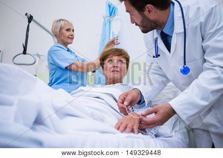 Doctor attaching iv drip on patient s hand in hospital room