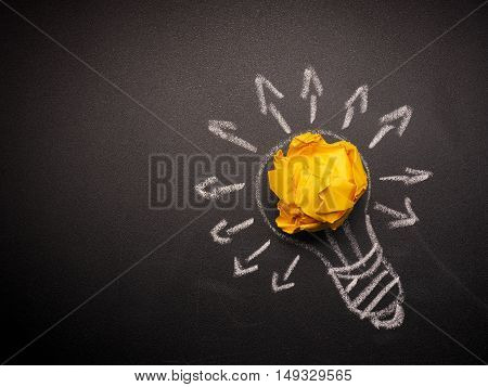 Crumpled paper with a hand drawn light bulb many ideas concept