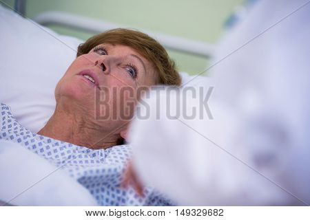 Senior patient lying on a bed in hospital room