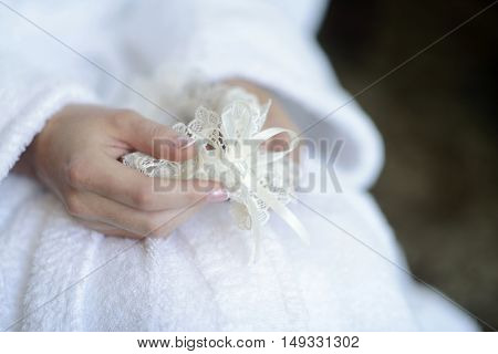 Beautiful bride in white dressing gown is holding garter in her hands. Beauty model girl in wedding robe. Female portrait with lingerie. Close-up woman's arms. Cute lady indoors