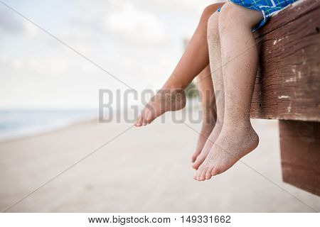 Small children sitting on the wooden pier in the water and enjoying summer day. Bare feet of boy and girl. Vacation by the sea. Outdoors. Siblings. Sister and brother by the ocean.