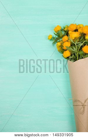 Bouquet of yellow flowers on turquoise wooden background. Top view on birthday bouquet. Flay lay. Lifestyle and holidays concept.
