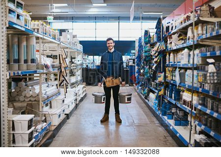 Young handyman posing in a hardware store standing smiling at the camera in the aisle between racks of merchandise