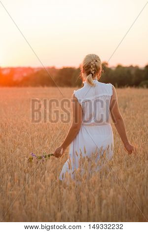 Back veiw on beautiful young woman walking on the rye field at sunset. Happy girl enjoying countryside life. Sunset on a farm. Lifestyle concept