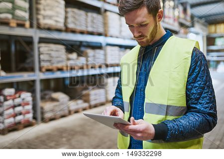 Young man shopping or working in a hardware warehouse standing checking supplies on his tablet with an absorbed expression