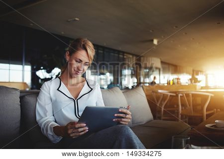 Female financier is reading financial news in internet via touch pad during work break in modern cafe. Confident woman lawyer is using digital table while is waiting client in an informal setting