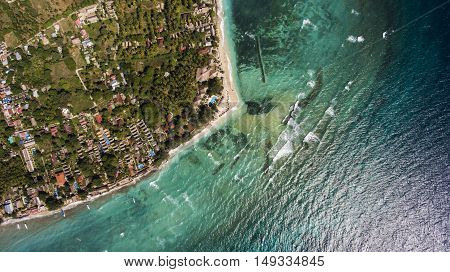 Top view aerial photo from flying drone of a beautiful Asian island with green plants and amazing blue color sea with waves. Beautiful nature landscape as background for your travel blog on website