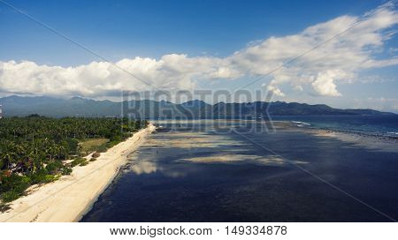 Aerial drone photo of beautiful coastline surrounded by a tropical landscape and jungle mountains. Small undeveloped island for a perfect calm holiday. Vintage noise effect