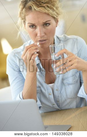 Woman at work taking pill to ease headache