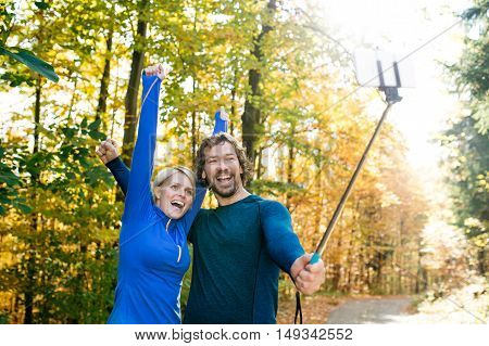 Beautiful young runners in colorful sunny autumn forest taking selfie with smartphone on selfie stick