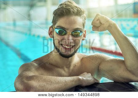 Swimmer man. Portrait of swimming athlete with goggles after training in waterpool.