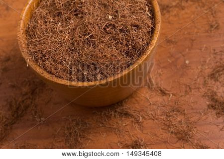 Dry Corn Silk Herb into a bowl over a wooden table. Stigmata Maydis