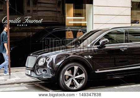 PARIS FRANCE - MAY 21 2016: Man admiring the luxury Bentley Bentayga Hybrid SUV on the streets of Paris France