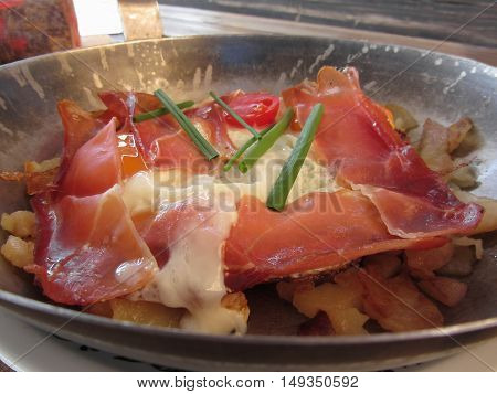 Typical South Tyrolean dish served pan fried with speck mountain cheese eggs potatoes and chive
