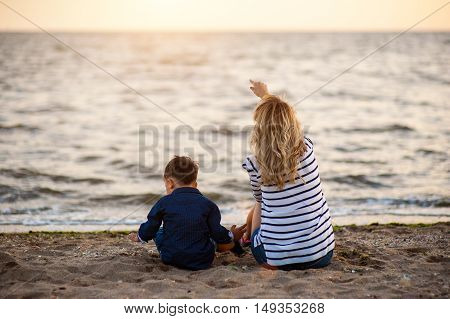 Beautiful woman with a child of four years playing on the beach near the sea