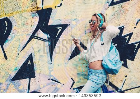 Young hipster girl with backpack wearing sweater and jeans relaxing and listening music against graffiti street wall