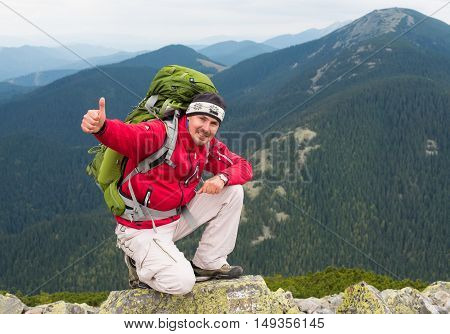 Happy hiker winning reaching life goal success freedom and happiness achievement in mountains. Thumbs-up. Hiker with backpack on top of a mountain.Concept of success