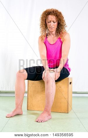 Serious Woman Holding Injured Leg