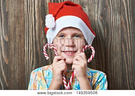 Little Boy In Red Cap With Two Christmas Candy Cane