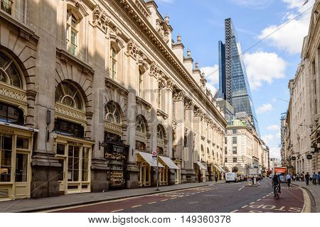 LONDON UK - AUGUST 21 2015: Cornhill street near Royal Exchange in London with a cyclist and a Leadenhall Tower by Richard Rogers on background a blue sky day