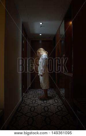 Sleepwalker Woman with white Bathrobe standing, head bowed, in the Hallway