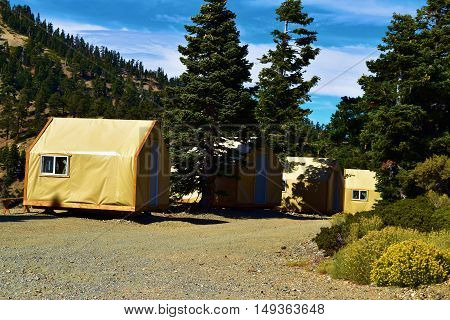 Row of modern rustic style tent cabins for a comfortable camping experience taken at a Pine Forest in Mt Baldy, CA