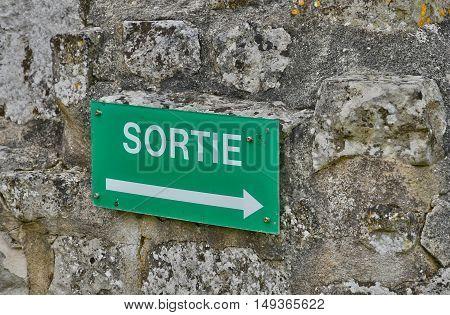 Saint Martin de Boscherville France - june 22 2016 : an exit sign on a stone wall
