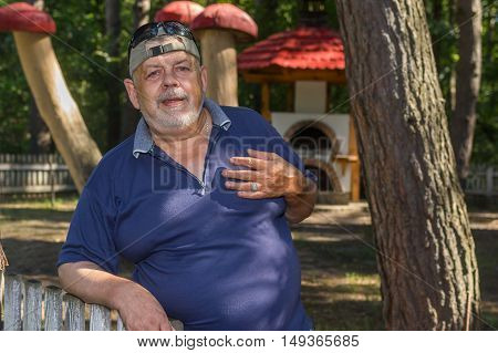Outdoor portrait of positive Ukrainian peasant standing behind wooden fence