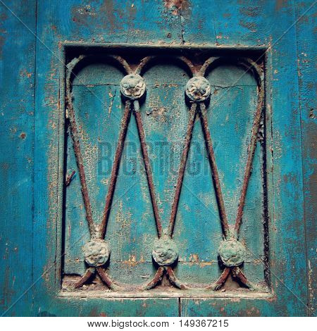 Wooden door painted blue with metal decorative elements. Cracked paint on the wood. Building exterior design feature. Venice Italy.