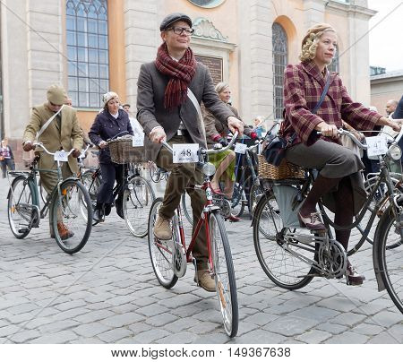STOCKHOLM - SEPT 24 2016: Cycling women and men dressed in old fashioned clothes in the Bike in tweed event September 24 2016 in Stockholm Sweden