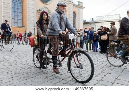 STOCKHOLM - SEPT 24 2016: Man and woman dressed in old fashioned clothes cycling on a tandem bicycle in the Bike in tweed event September 24 2016 in Stockholm Sweden