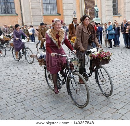 STOCKHOLM - SEPT 24 2016: Smiling cycling women dressed in old fashioned dress in the Bike in tweed event September 24 2016 in Stockholm Sweden
