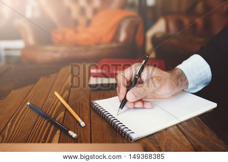 Personal and business correspondence. Unrecognizable man in suit writes text in notebook. Business, work, author, writer, planning, creative concept