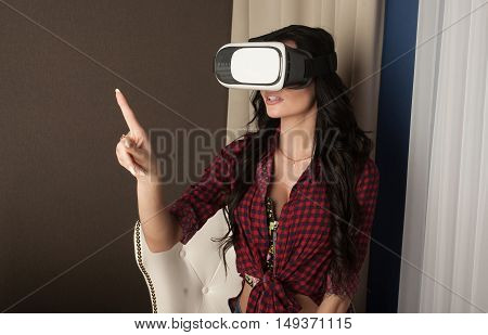 Sexy brunette woman in red shirt with glasses of virtual reality. VR concept.