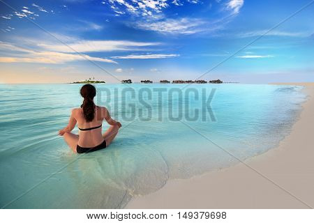 Young woman exercising yoga in turquoise lagoon with overwater bungalows around tropical island