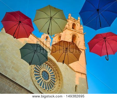 Six Colorful Umbrellas Against Gothic Cathedral And Blue Sky.