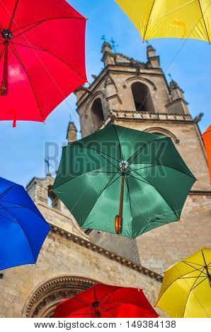 Colorful umbrellas against campanile of gothic basilica of San Pedro in Reus Spain. Vertical.