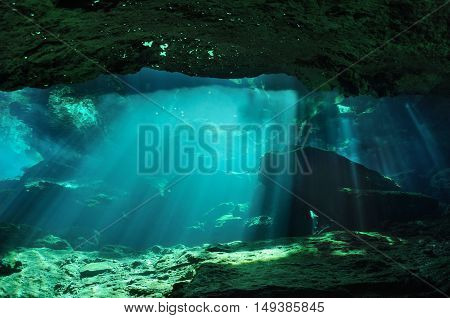 Sunbeams penetrate through the waters of Chac mool cave producing mysterious reflections on the surface in the background, Yucatan peninsula, Mexico