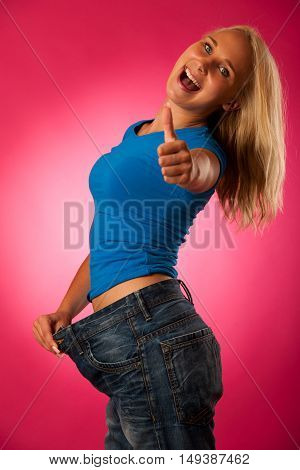 Healthy Lifestyle - Fit Blond Woman With Too Big Trousers Gesturing Weight Loose