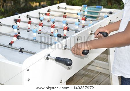 a hand of a foosball gamer playing in a park