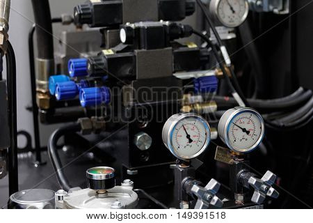 Hydraulic system of cnc machining center with gauges to control pressure. Selective focus.